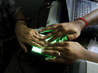 Image Credit: NPR and Bikes Das/AP (Shown: An operator helps an elderly woman scan her fingerprints in May 2012 as she enrolls in an identification project called Aadhar in India. The giant effort, which aims to give every Indian an identity record and number for the first time, involves recording retina scans, fingerprints and photographs of all 1.2 billion Indians).